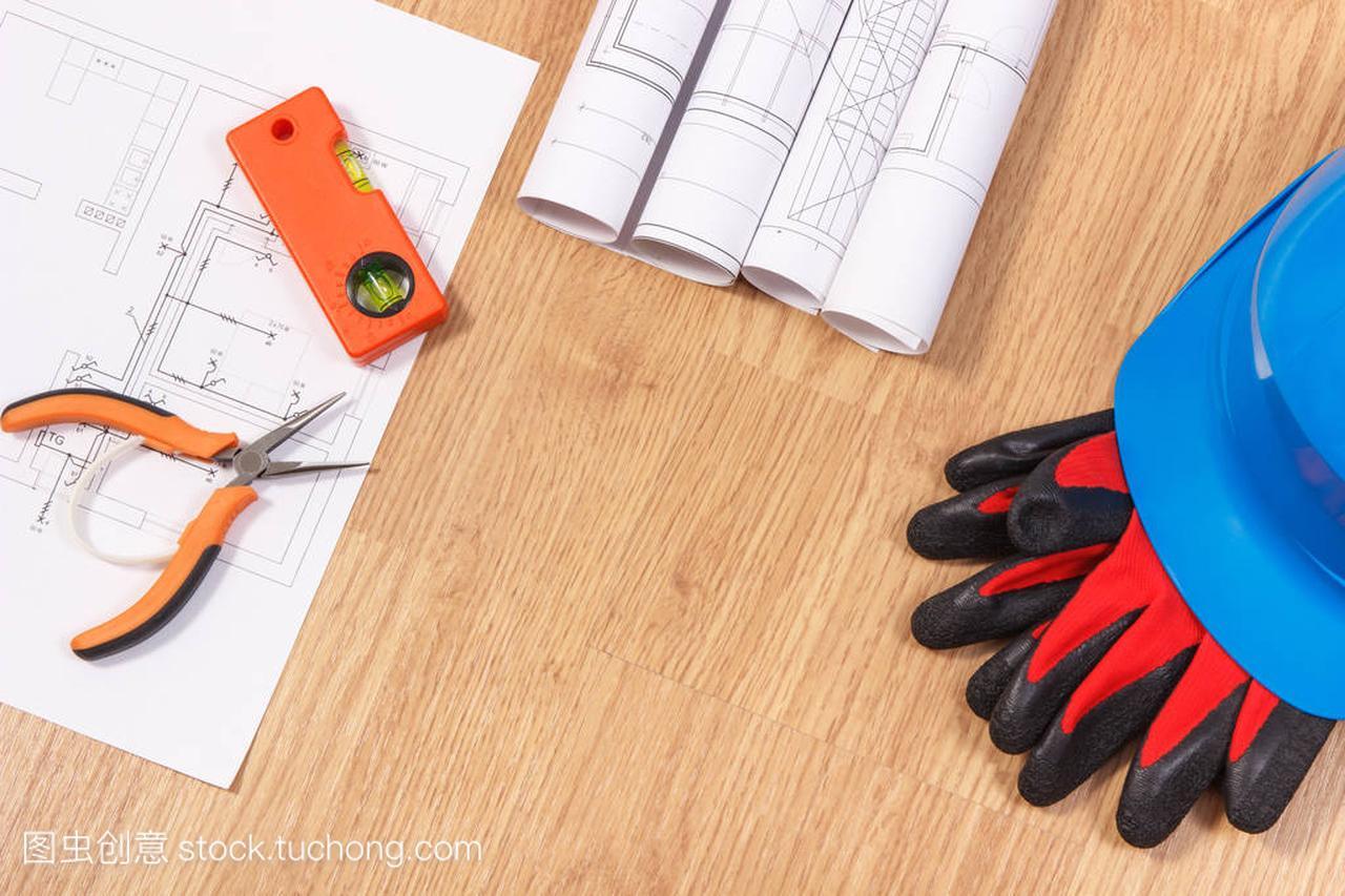 电气设备或图、防护橘子图纸和手套工作头盔三角图纸工具上的图片
