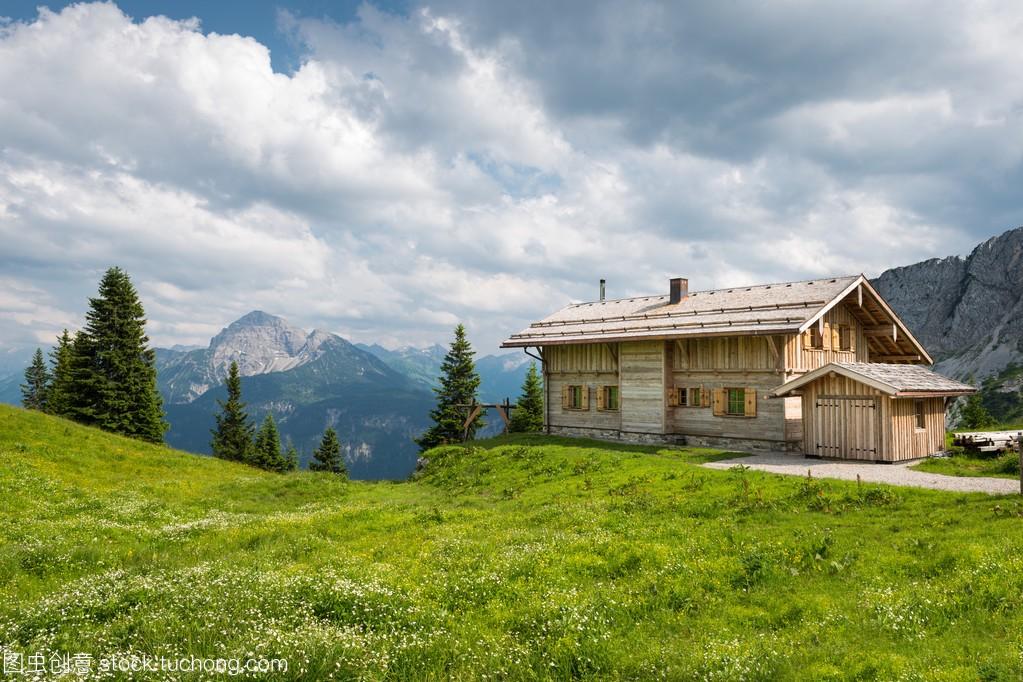 在春天的奥地利山上木别墅木屋别墅尖山木材图片