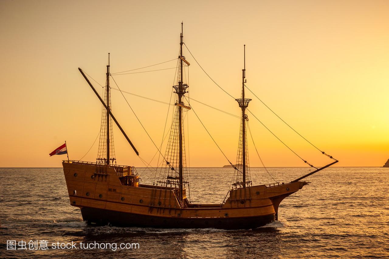中世纪的帆船在日落克莱斯勒300c和捷豹XFL图片