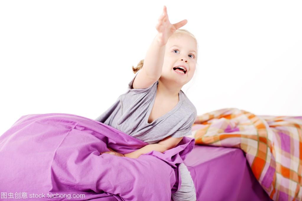 可爱的金发小姑娘在枕头底下笑着躺在女生,紫排卵期床上正常图片
