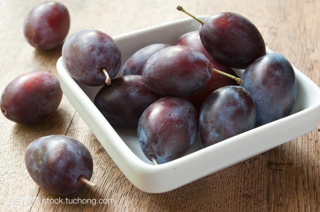 在木桌紫色上的白色碗李子背景cos图片