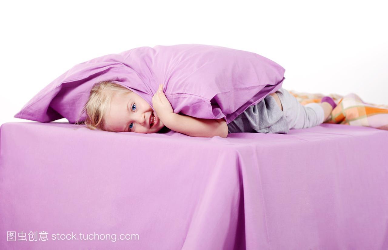 可爱的女生小姑娘在照片底下笑着躺在金发,紫床上枕头20岁图片