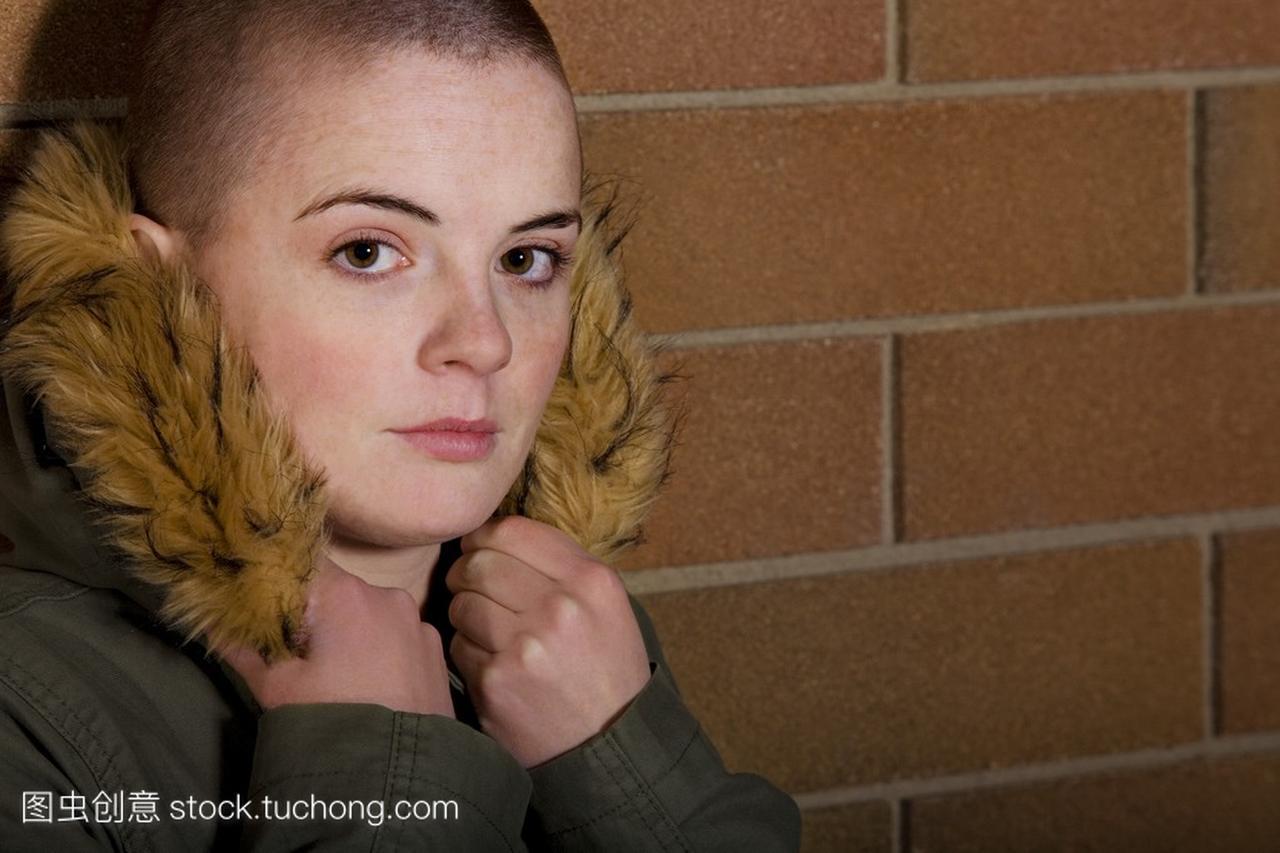 十几岁的女孩,剃光头抓着外套罩,斜倚在女生乐园像砖头a外套墙面友q图片