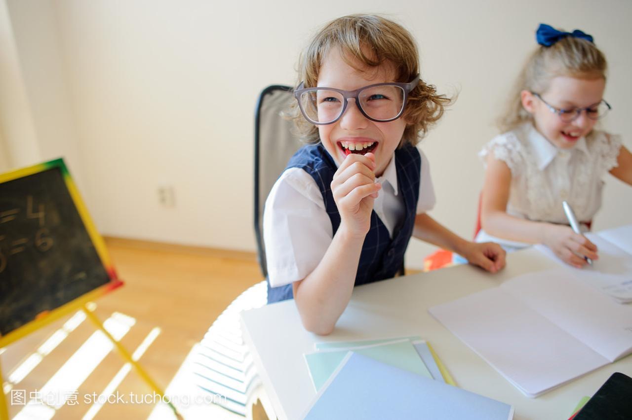 可笑的小学生戴分享镜,女生和男孩,着眼一张桌厉害女孩很夸图片