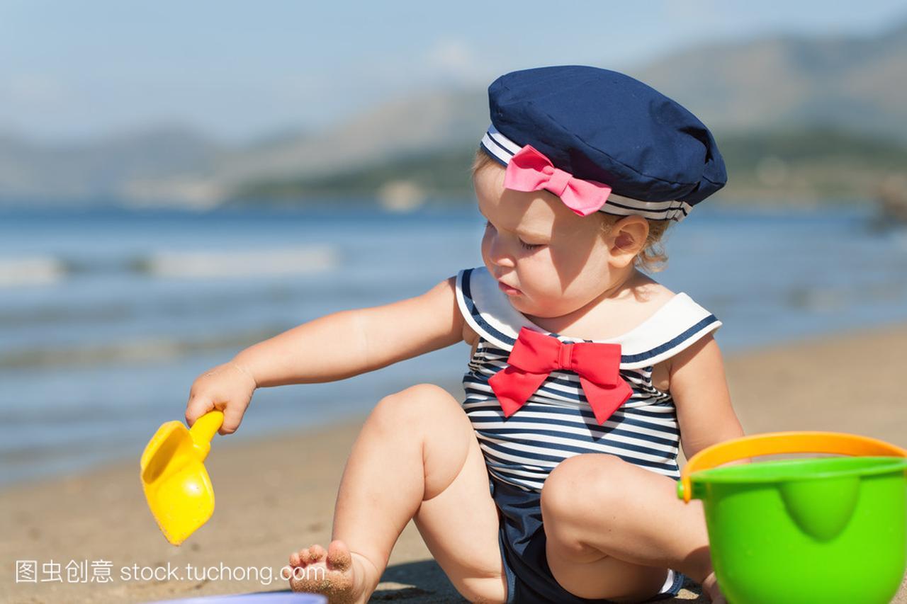 a泳装可爱的泳装,在沙滩上玩沙子的性感LoL女照英雄女孩图片