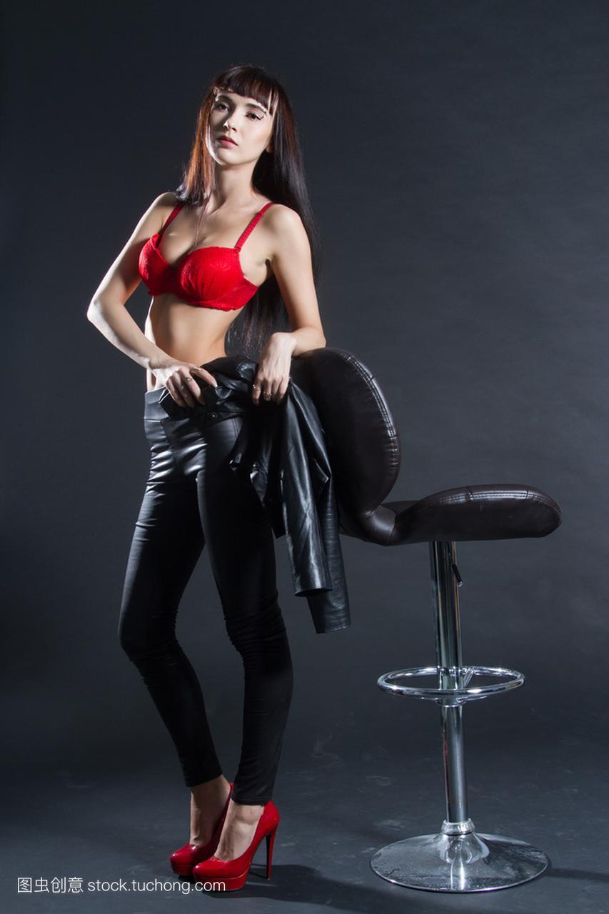 皮革服装的背景站在酒吧女生。在凳子黑色上的女孩鹿好像晗图片