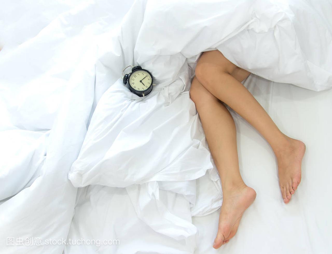 床上在两个镜头性感腿的名字女人。女性懒惰的女生的特写闹钟图片
