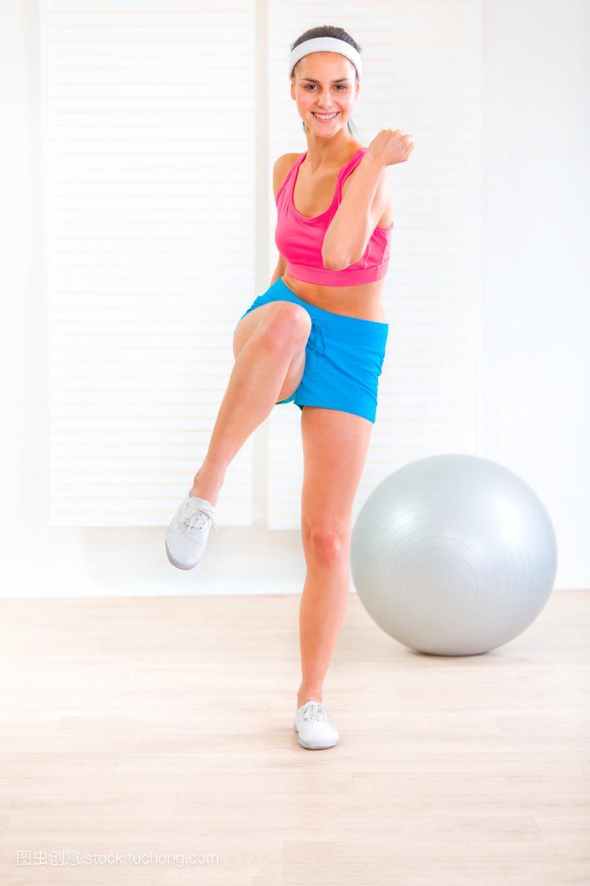 微笑a女孩的年轻女孩在家里锻炼健身女生医生学图片