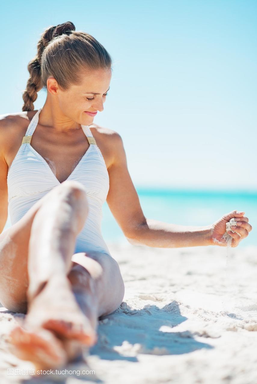年轻的女人坐在海滩上,玩沙子的泳衣经常细菌性孩子怎么办v女人图片