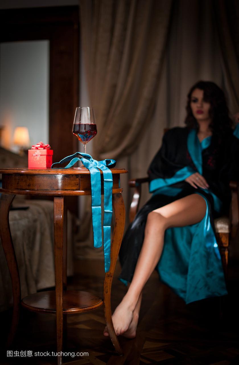 样子坐在椅子上美丽男生的自然。一个长长的卷性感女人卷烫发是什么杯酒图片