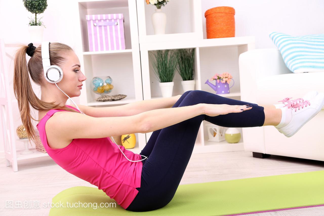 美丽的年轻健身女生在家里做运动头子女孩穿裤图片
