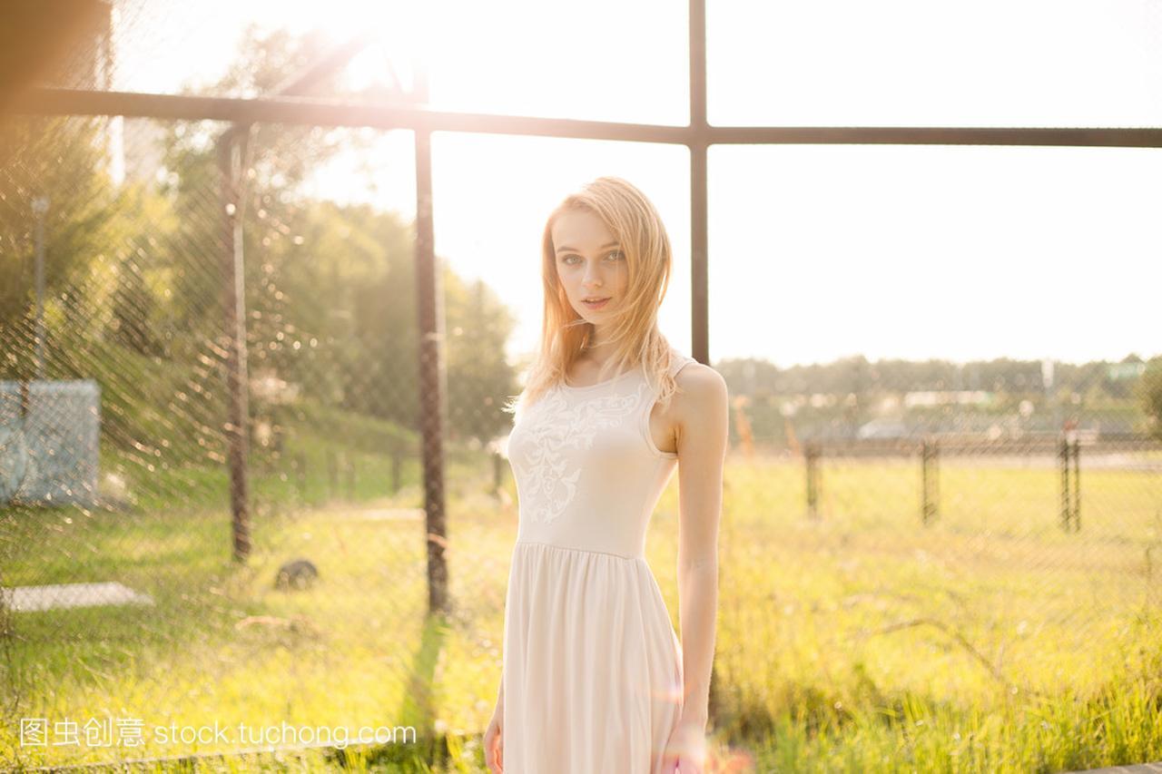 在白色里那天女孩美丽的阳光连衣裙的公园胸女生明媚的图片