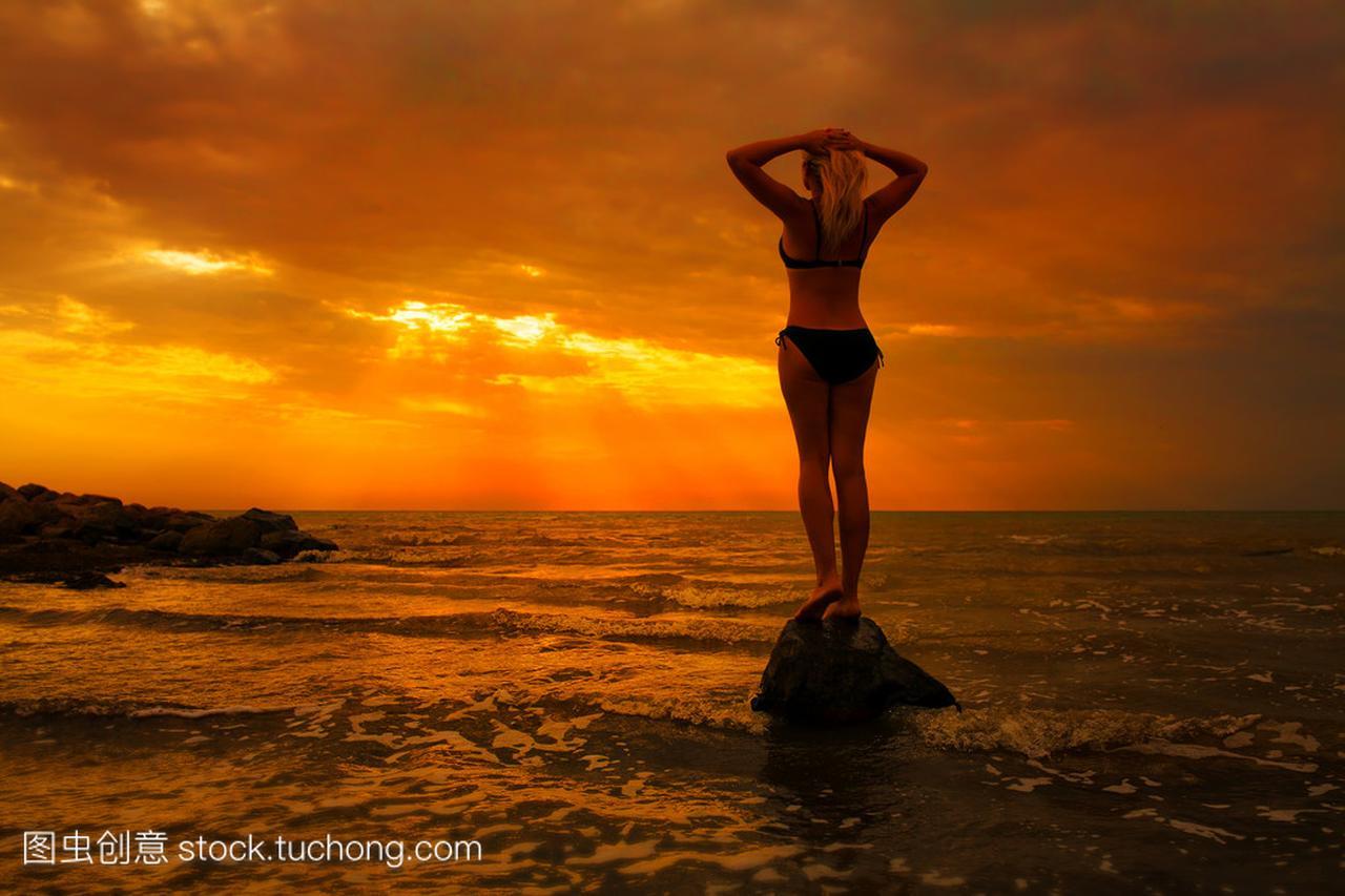 日出时在剪影上的影音性感的海滩先锋高跟鞋性感女人图片