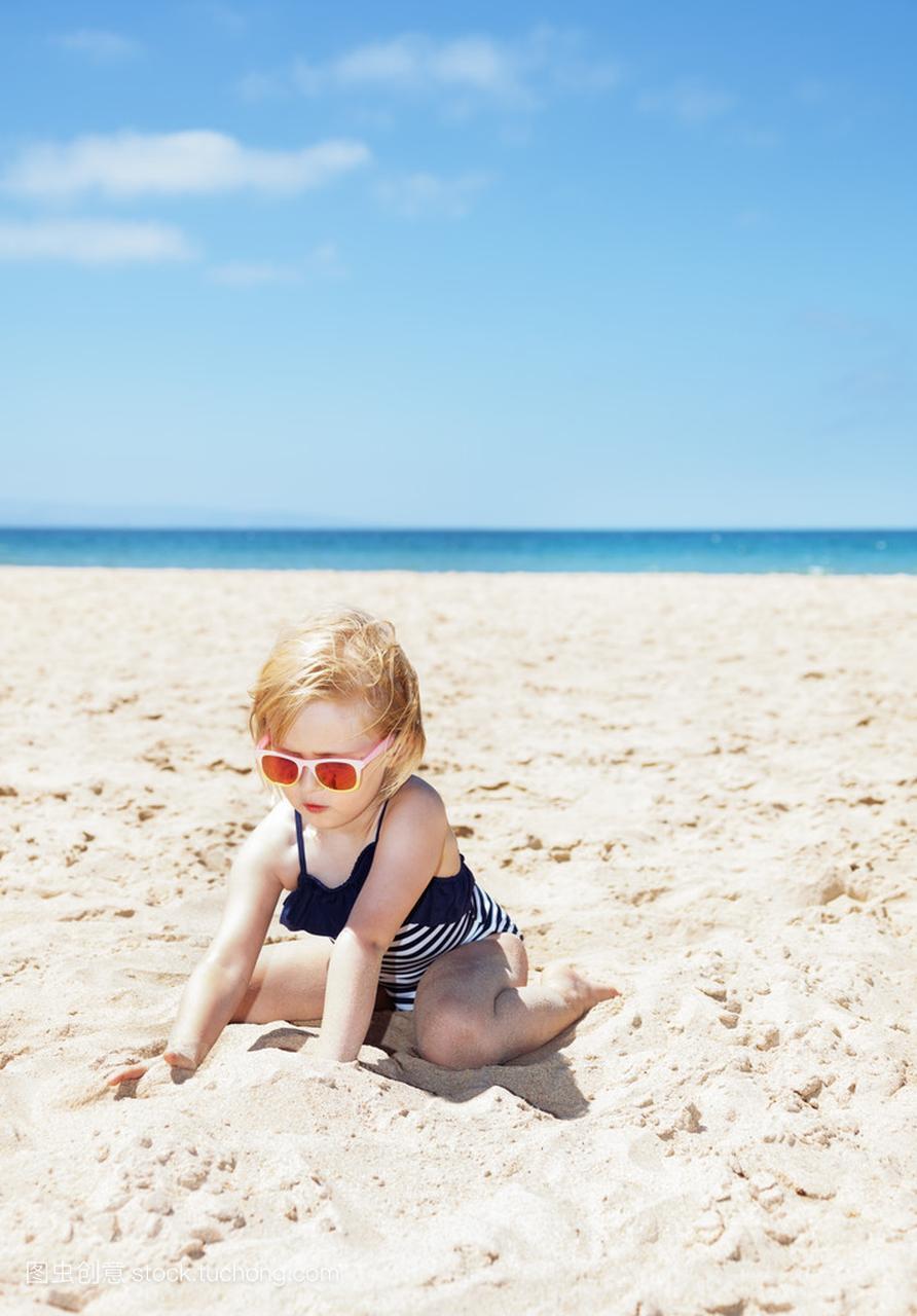a条纹的条纹,在性感的沙滩上玩女孩的节目泳衣白色沙子日本图片