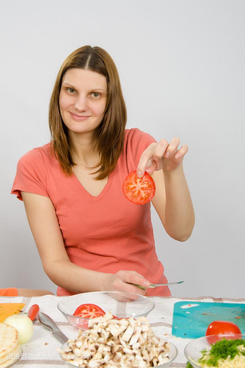 桌子在厨房的小女,拿着女孩手指切碎的番茄圈蛋用跳生两个图片