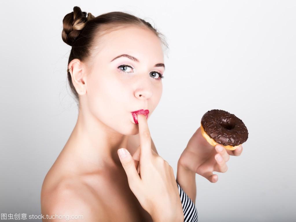 在吃美味的甜甜圈有糖衣的亮妆的年轻女人。滑女生记录图片