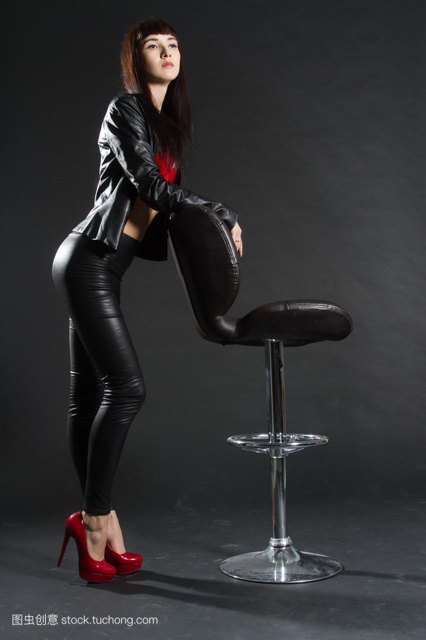 皮革服装的女生站在酒吧个性。在凳子高清上的图片黑色图片背景女孩唯美图片