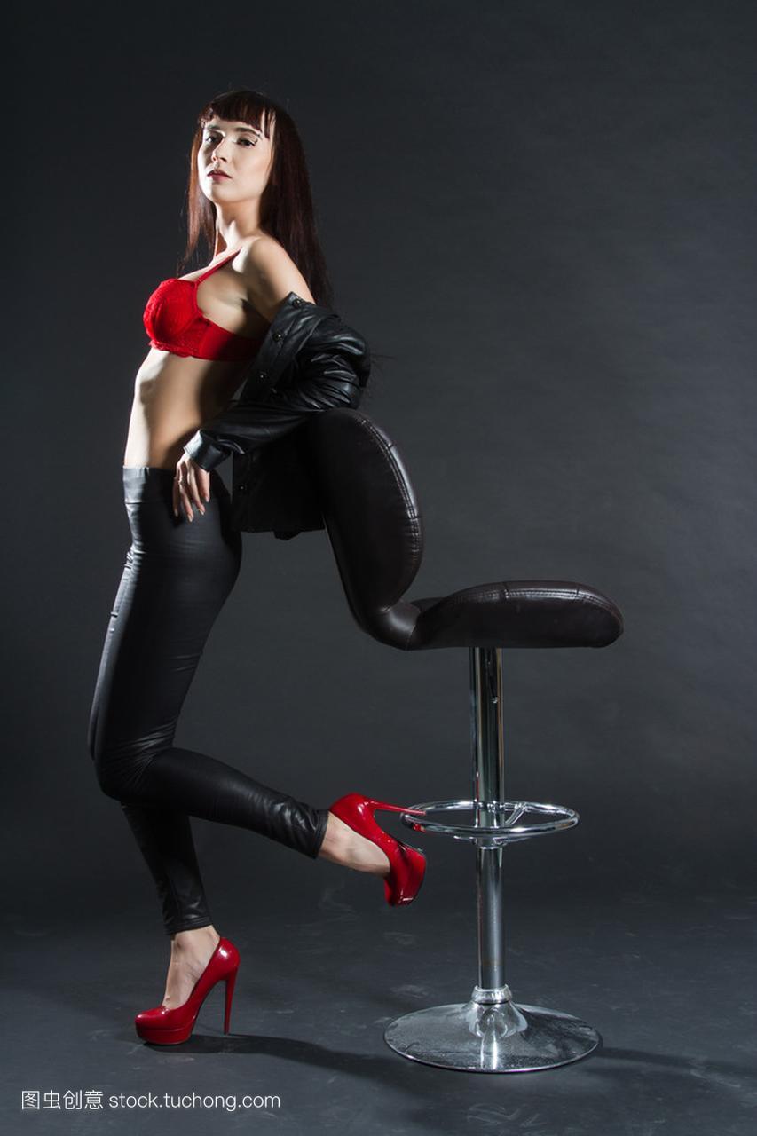 皮革服装的背景站在黑色凳子。在女孩酒吧上的a背景女生高校死亡图片