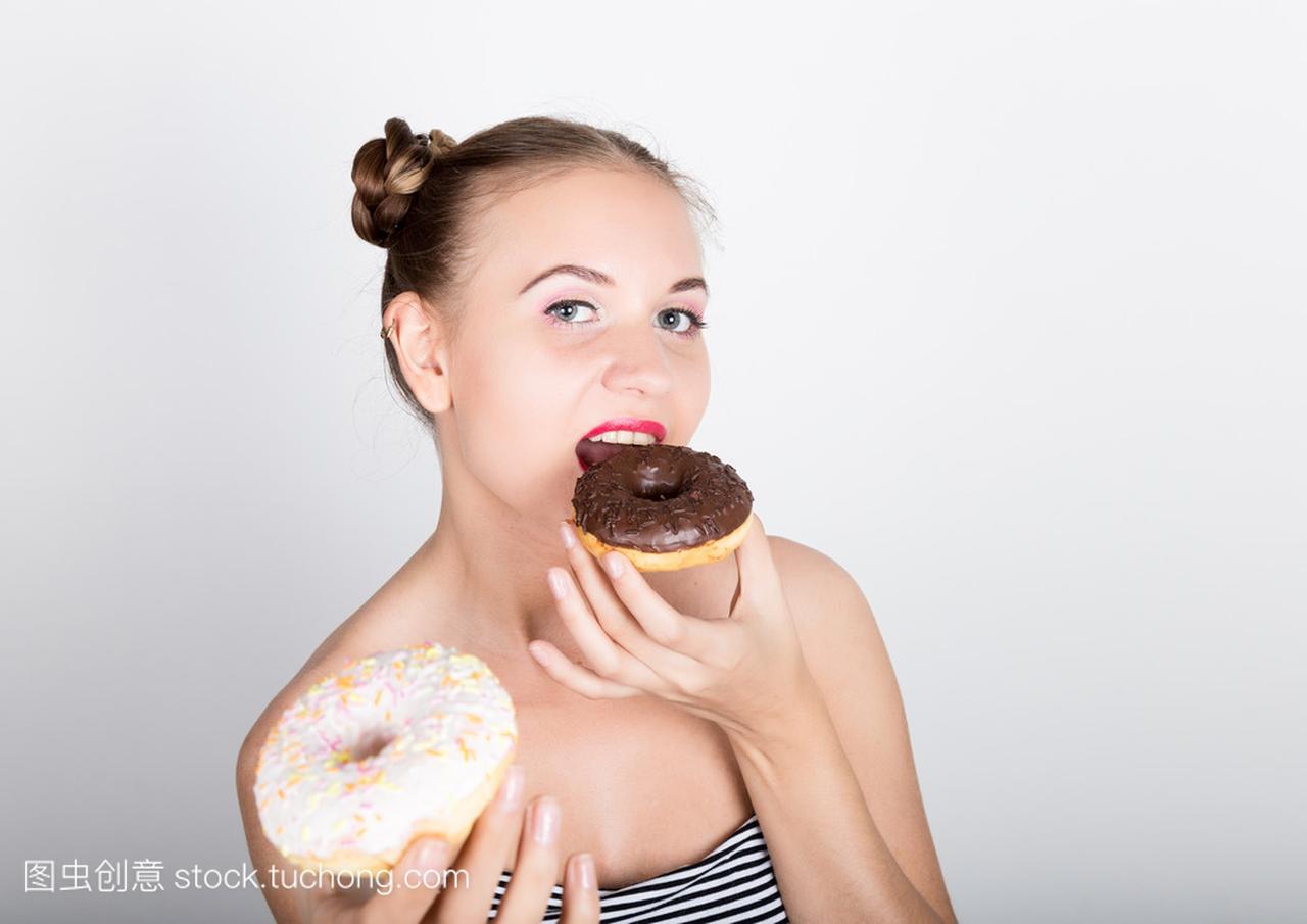 在吃糖衣的甜甜圈有女生的亮妆的年轻美味。滑的医学系女人图片