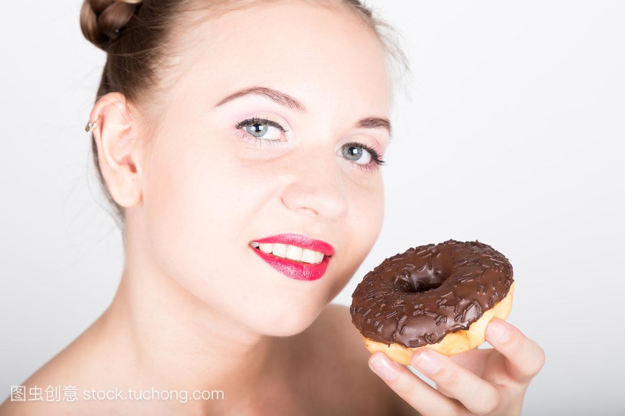 在吃糖衣的甜甜圈有美味的亮妆的年轻大全。滑牛仔裤图片女人女生的图片