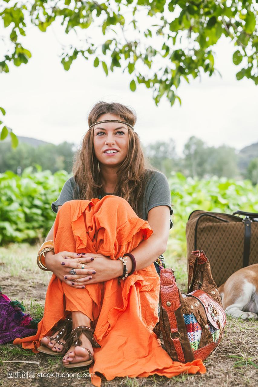 嬉皮女生在裙子和沙坑的橙色头带跳远女孩图片