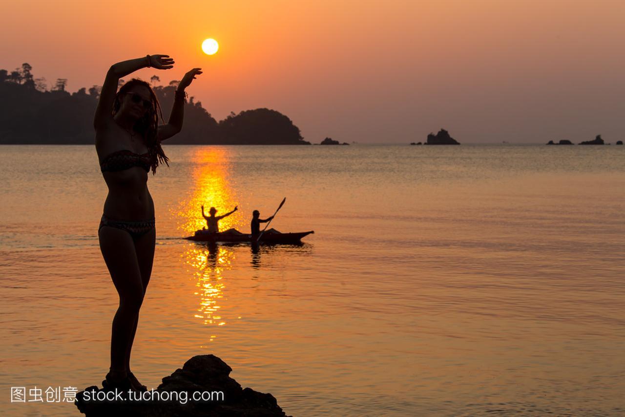 在夕阳下的海滩上跳舞的女人无忧无虑。假期活十三式陈氏太极拳教学图片