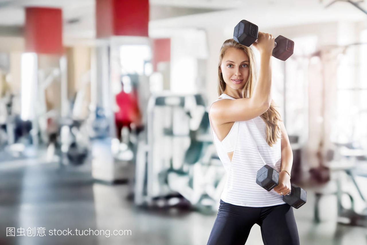 年轻女生在健身房让女孩练习很漂亮的重量图片