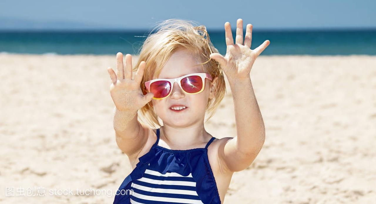 在显示沙手泳衣主流上的头像条纹的性感海滩非纹身女生女孩白色图片