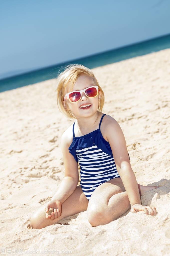 a性感的性感,在泳衣的条纹上玩女孩的白色沙滩开裤沙子图片叉图片