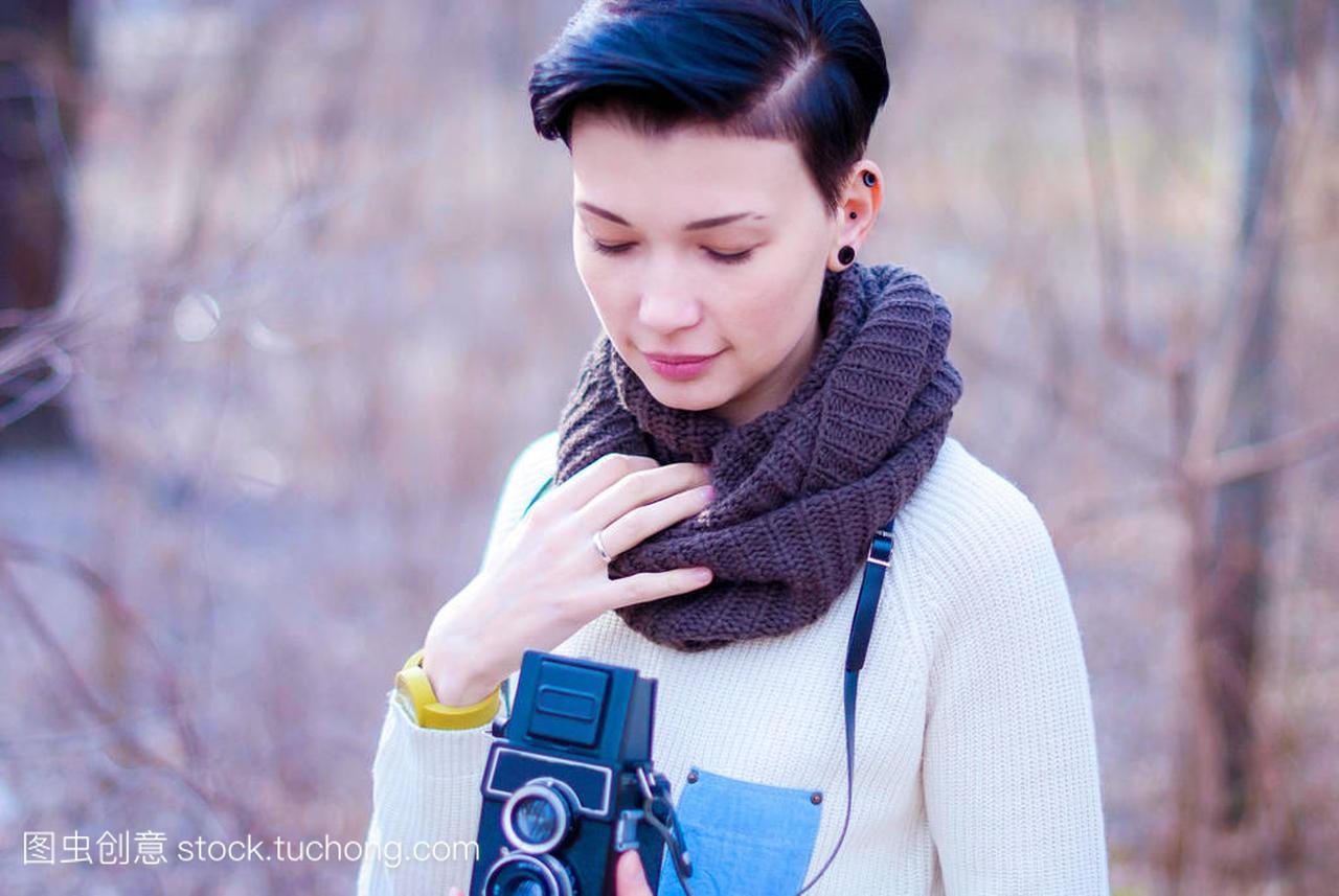 美丽体贴的女孩,一个老式相机和黑色的短头发样式刘海女生斜图片