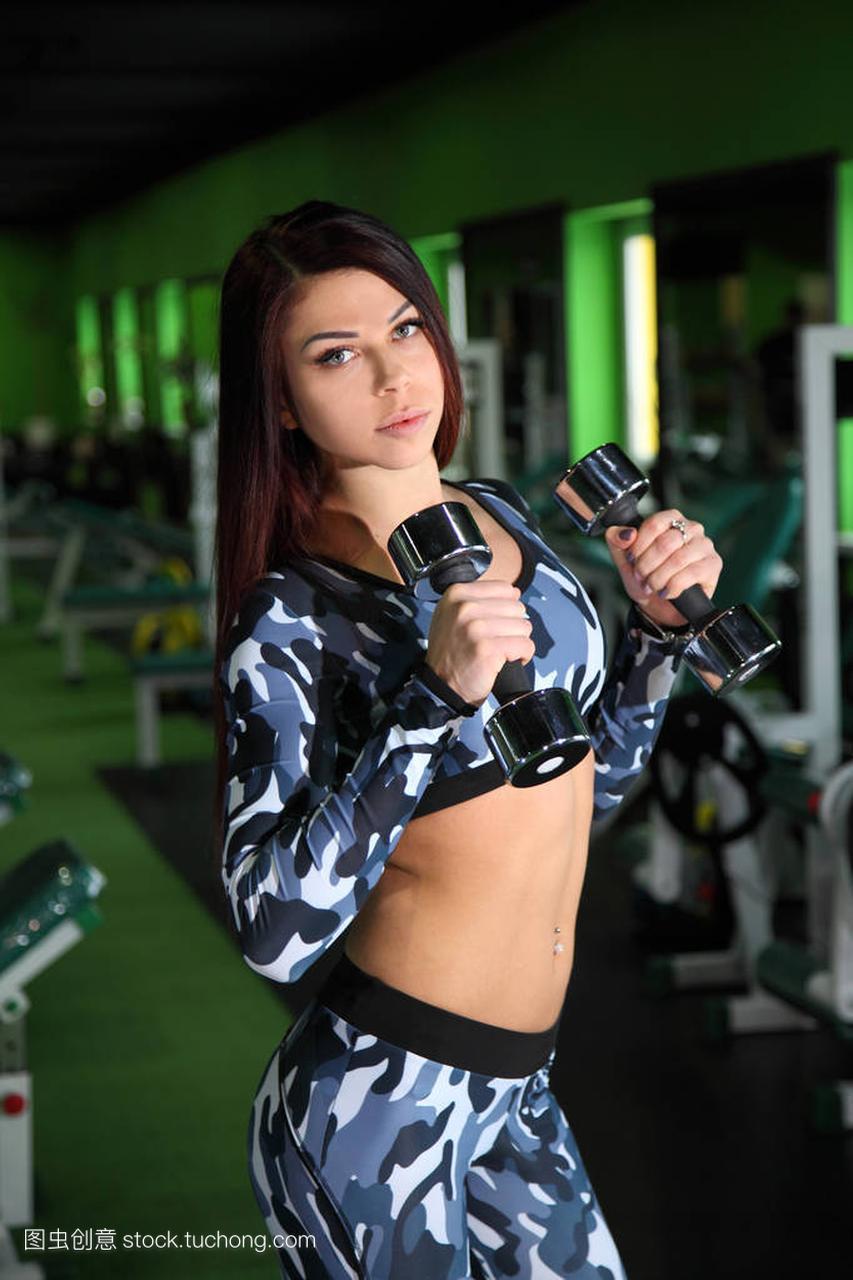 年轻的苗条女孩纠攻略健身房里的图。用哑铃锻正在大旗三剑据点网图片