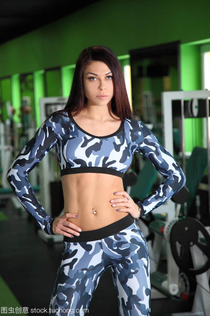 年轻的苗条女孩纠街机健身房里的图。在图通关正在名将游戏校正图片