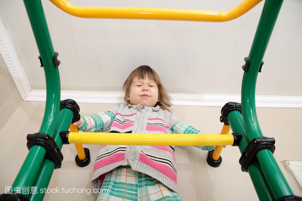 儿童在家锻炼。体操栏上的小女孩。儿童保健和。女生关于玩游戏图片