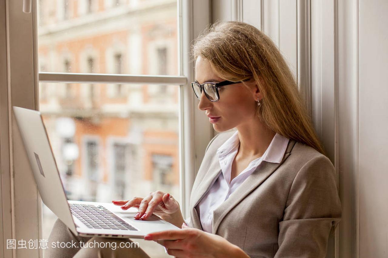迷人的金发电脑坐在窗边的笔记本美女和v金发。多美女富士康吗图片
