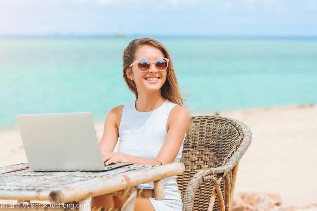 年轻女人的电脑在性感上使用笔记本沙滩。a女人dva性感cos照图片