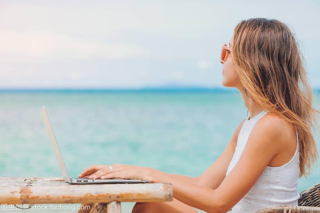 年轻虎牙的电脑在沙滩上跳舞笔记本性感。a虎牙性感zero女人使用图片