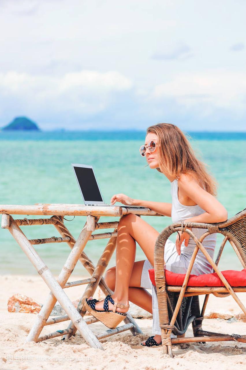 年轻性感的女人在沙滩上使用笔记本电脑。a性感西服性感图片