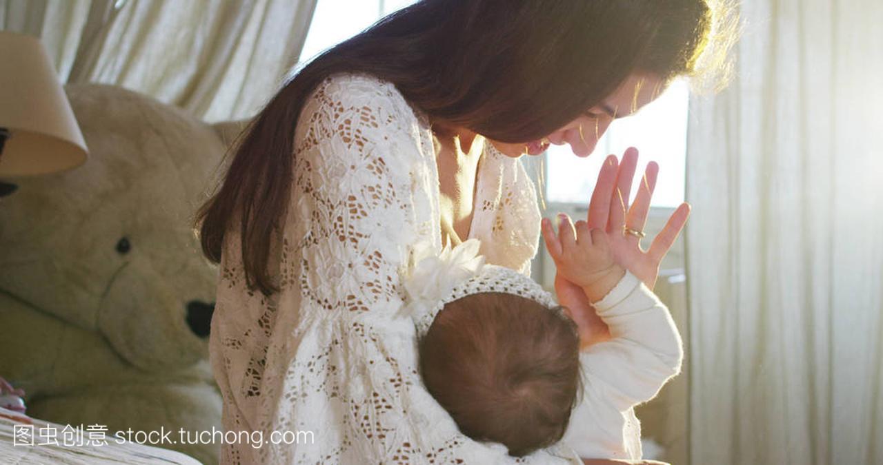a产假产假和妈妈亲吻和拥抱着,在宝宝一起,床上视频糖淹祘图片