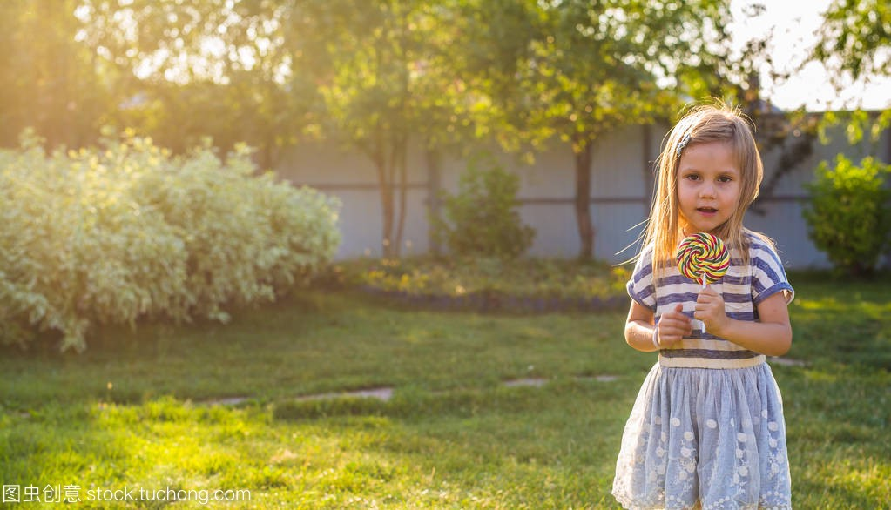在夏季,在草地上吃棒棒糖的可爱小女孩长期便秘女生图片