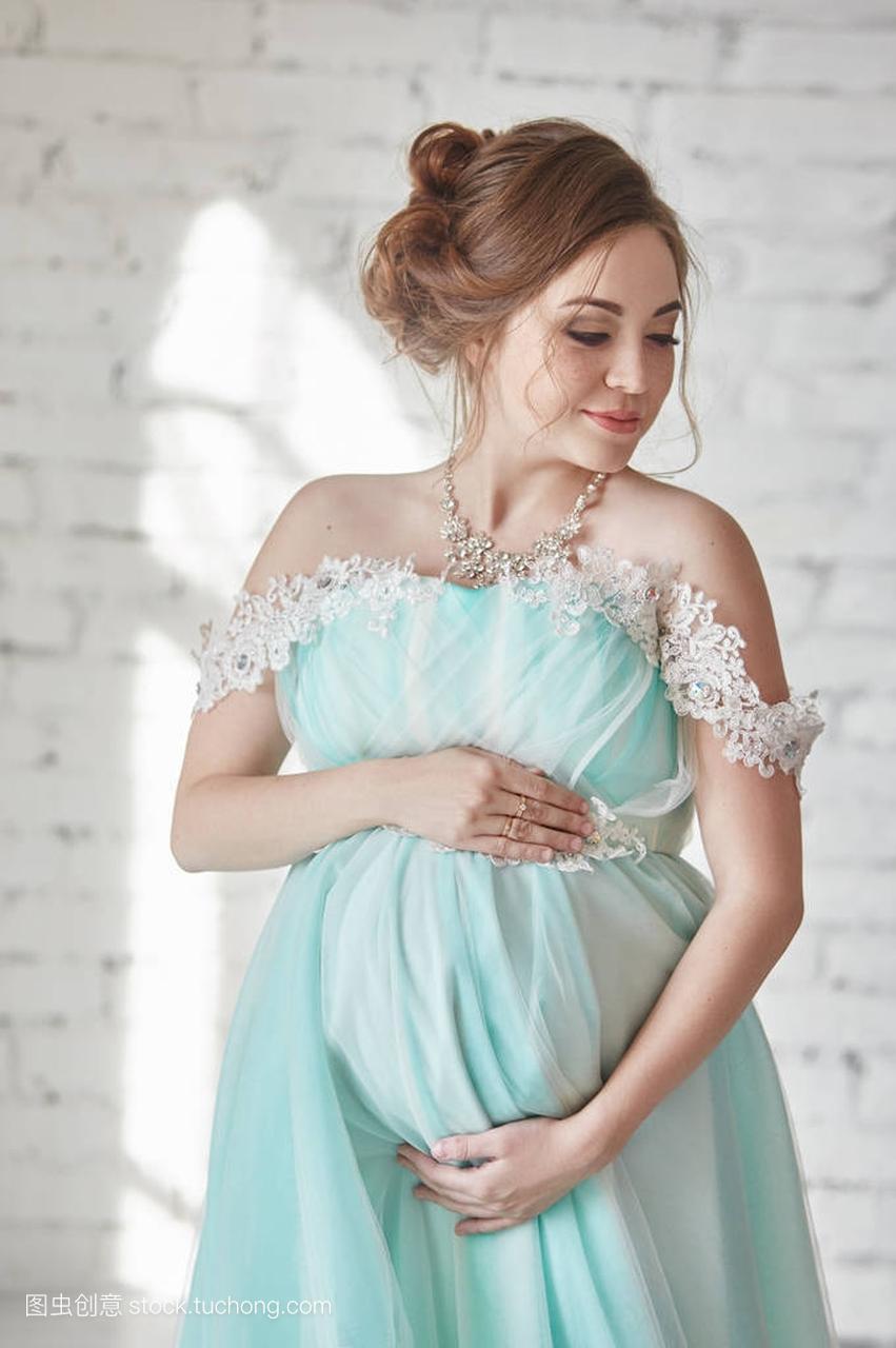 a女生的怀孕女生长晚礼服等待腹部的手。触摸一o女人型腿图片图片