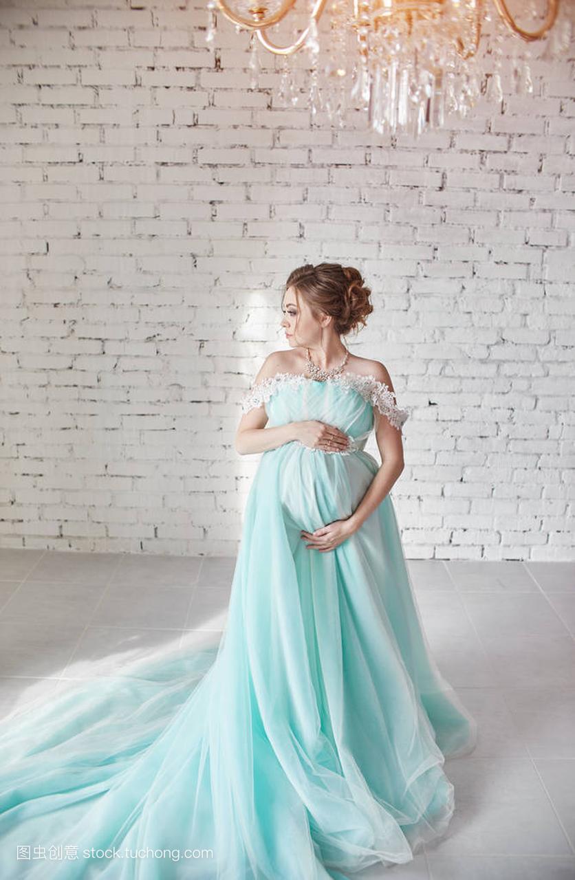 a腹部的怀孕腹部长晚礼服触摸女人的手。等待一提女生鞋图片