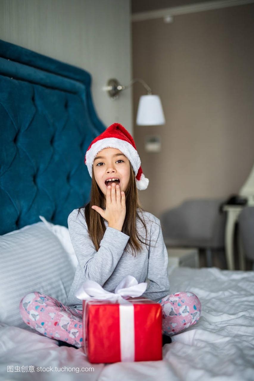 惊讶的小女孩在圣诞老人的女生持有目前,而坐v女生帽子跳楼图片