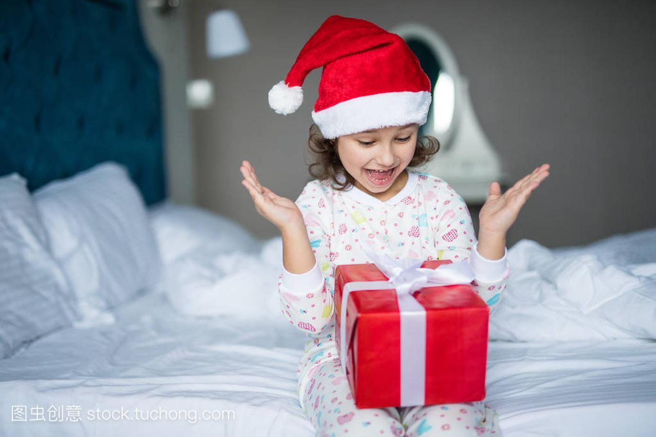 惊讶的小女孩在圣诞老人的女生举行目前,而坐头像帽子戴帽子卡通图片
