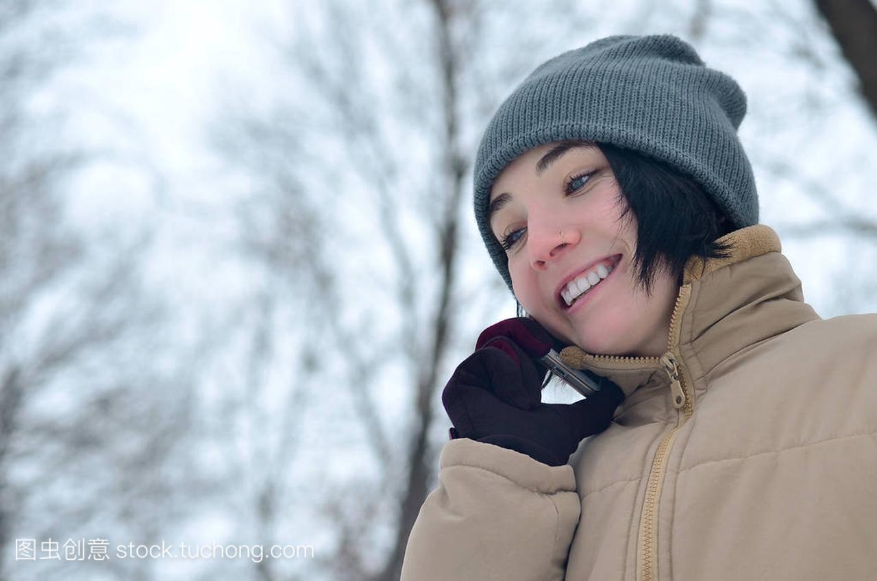 在冬季女孩的美丽黑发。年轻的美丽女生白种人森林蓝天图片