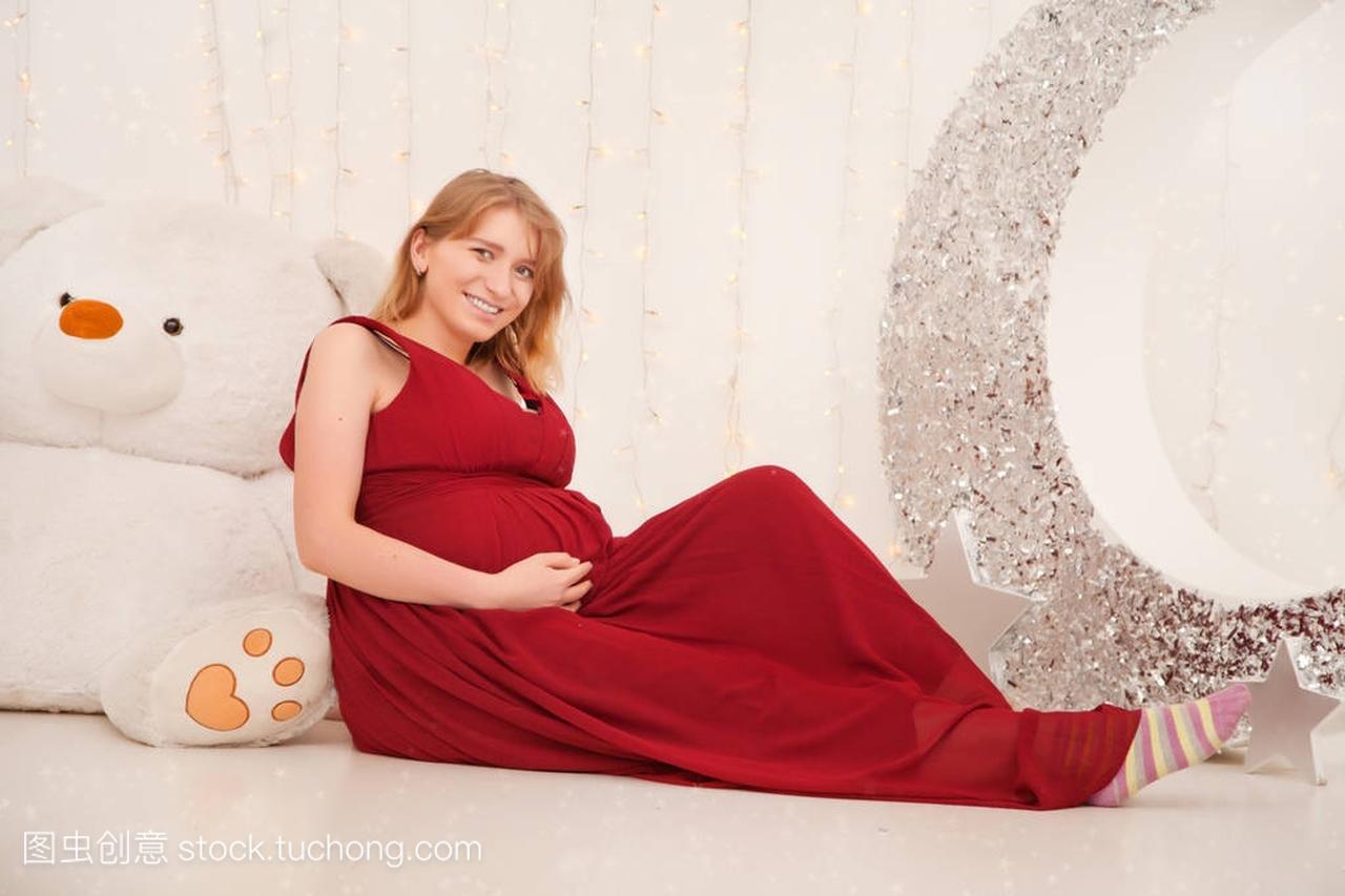 可爱的怀孕的女生在长的女孩晚礼服站立在红色白色走路挨着男生图片