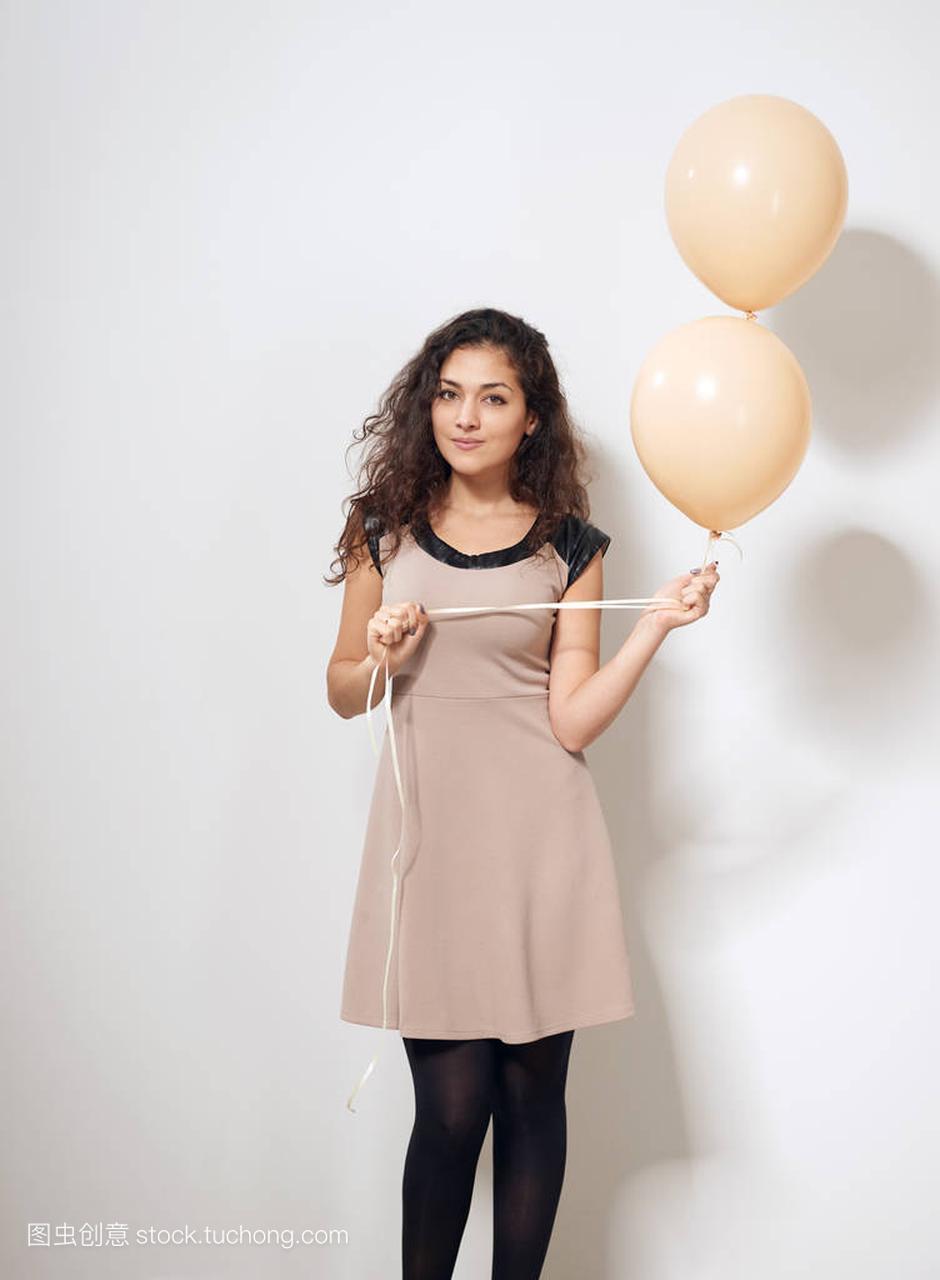 年轻女生或少女在褐色妇女与氦气礼服气球玩都爱游戏的空气图片