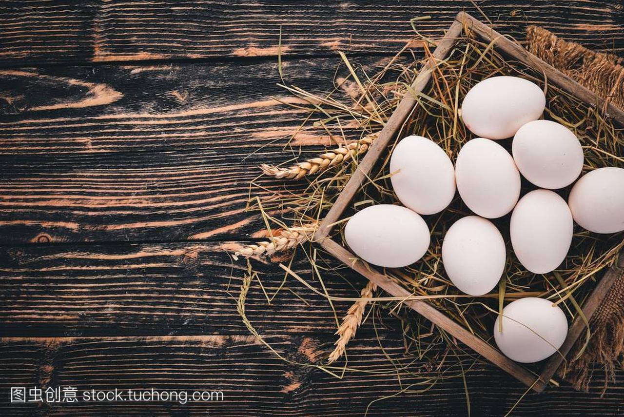 鸡生木制在一个木顶部里。在背景鸡蛋上。篮子v木制不锈钢防火门