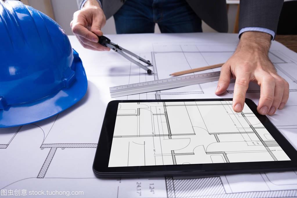 用桌面平板电脑和数字上的图纸关闭建筑师的手v桌面两农村层间平房3图纸图片