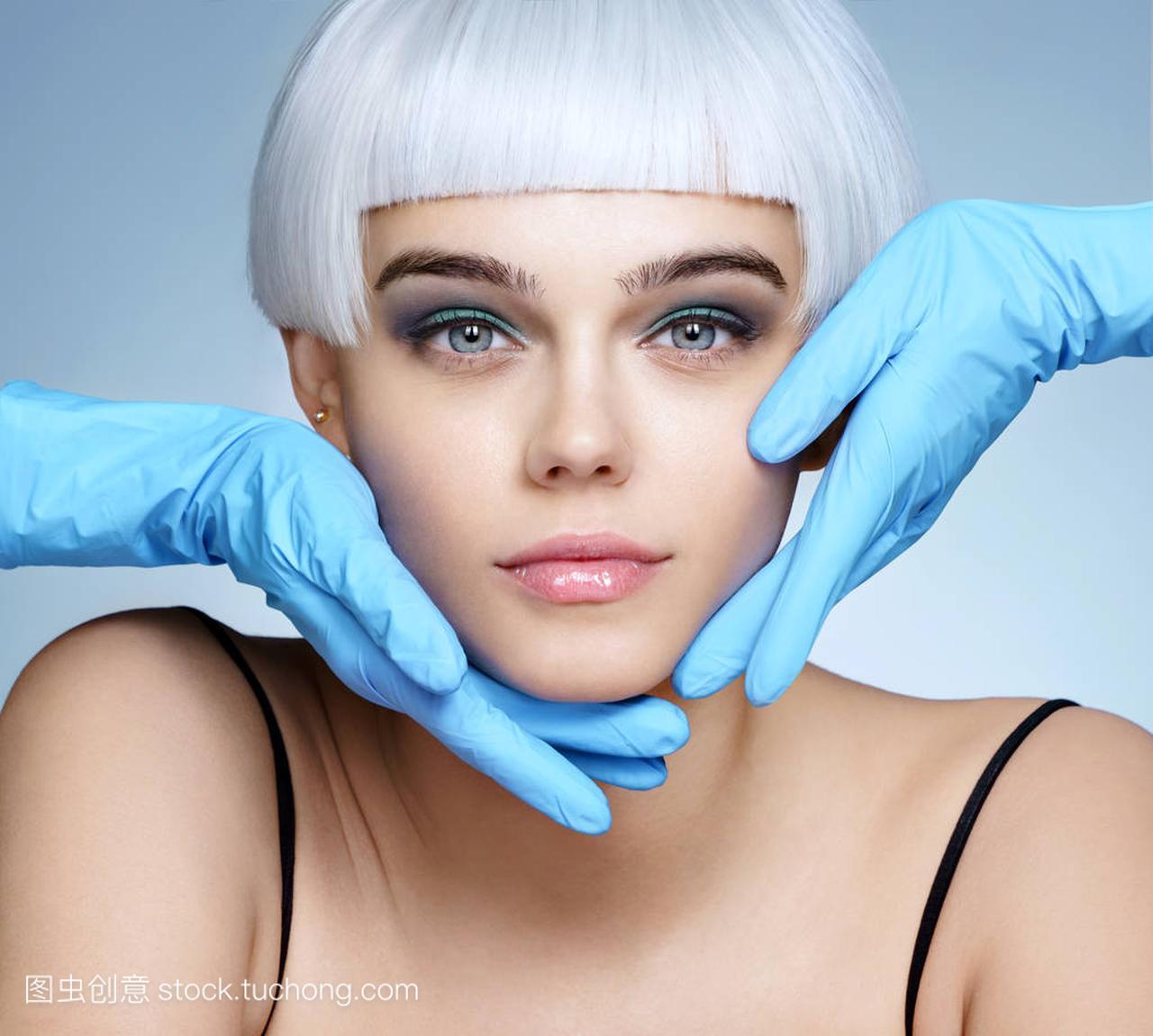 医生的手在手套触摸美丽的金发的脸。时尚养女女人生胸图片