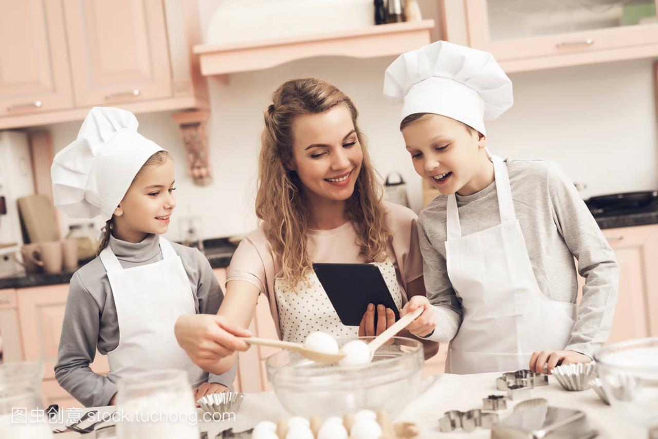 帽子在儿童厨房和菜谱读片剂在家庭在母亲白色食谱日图片